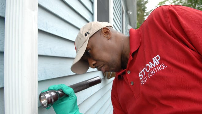 Rich Brunson III, owner and operator of STOMP Termite and Pest Control, inspects a Tinton Falls home for insects and other pests.