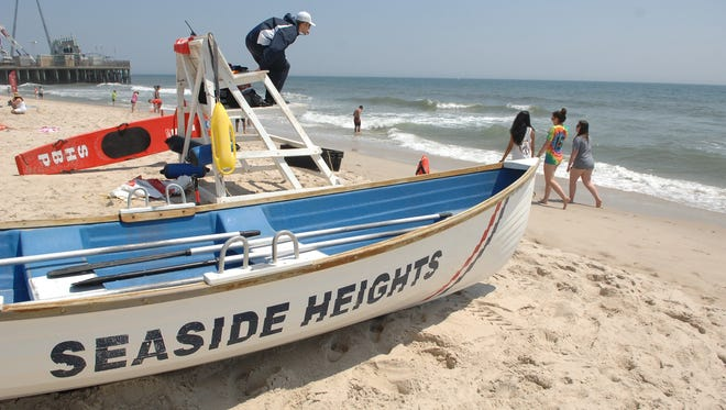Beachgoers stroll in front of a lifeguard on the beach in Seaside Heights on Saturday, May 28, 2016.