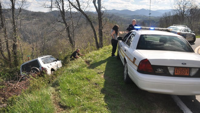 Law enforcement gather evidence around the accident scene following the high-speed chase.