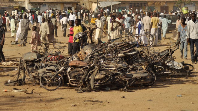 People gather at the site of a bomb explosion, in Kano, Nigeria, on Nov. 28, 2014.