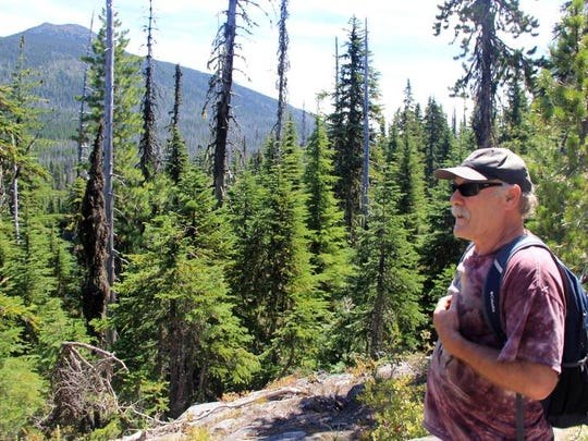 """Michael Donnelly looks out across the Ollalie Lake Scenic Area during a recent """"lake bagging"""" trip."""