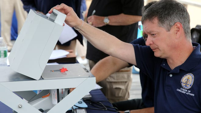 Inspectors from the Department of Consumer Affairs test for lead amounts in small toy prizes that could be won in the arcades of the Point Pleasant Beach Boardwalk.