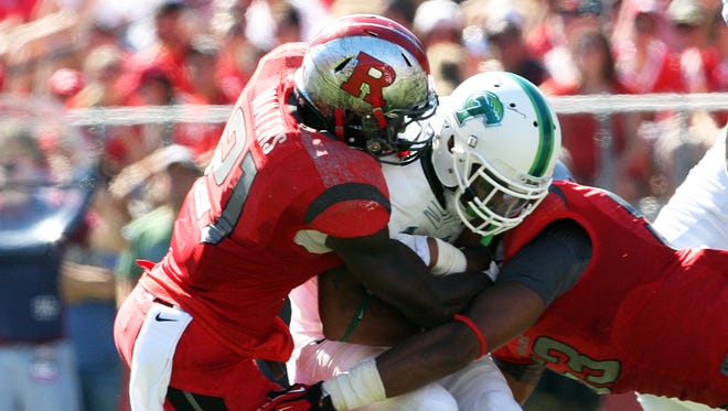 The Tulane Green Wave take on the Scarlet Knights of Rutgers at High Point Solutions Stadium in Piscataway for an afternoon NCAA football game.  Rutgers # 21 (left)- Lorenzo Waters & # 53 (right)- Julian Pinnix-Odrick combine to bring down Tulane's # 3 (center)- Sherman Badie.  On Saturday September 27,,2014 Photo: Mark R. Sullivan/Staff Photographer