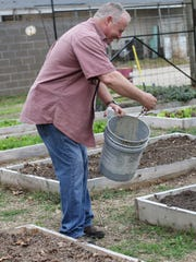 Stewart Robinette tosses a handful of worms into a raised bed in the Let's Grow Monroe garden behind The Assembly South on South Eighth Street on Thursday. The garden is organic so pesticides and fungicides are not allowed. Worms play a key role in helping fertilize the soil.