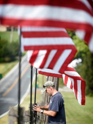 Travis Goebel secures American flags to the fence posts at 1536 Old Forge Road in Annville. One hundred flags will be displayed for the upcoming bebefit and music festival. The flags will offerd for sale and profits donated to the Wounded Warrier organization. Fogleman's Wounded Warrior Music Fest kicks off September 10, 9 a.m. to 11 p.m., (rain or shine) at the Fogleman Farmstead, 1536 Old Forge Road, Annivlle, PA. Live entertainment starts at 2 p.m. The BYOB event will feature a pig roast, open pit chicken, hamburgers, hot dogs, and homemade cast-iron kettle soup. The family friendly event will feature singer Olivia Farabaugh, Shift Seven with guest singer Pam Weaver of Steel Kitty, Flamin' Dick and the Hot Rods, Applejack, The Youngers, The Matt Creter Band, Whiskey Tree, and the Honkey Tonk Medics. Organizers expect to roast seven pigs, fry 1,200 chicken thighs for an expected 700 vistors. Last year the festival raised $25,000.00 dollars.