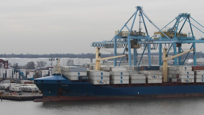 Chiquita shipping containers are loaded and unloaded from a waiting cargo ship at the Port of Wilmington.