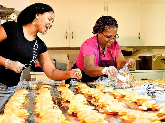 Ja'Lia Lopez, left, and kitchen manager Cecelia Harris, right, with Abundant Life Ministries, share a laugh as the group works to prepare 1,000 lunches Thursday at New Covenant Community Church. Each Thursday, the organization distributes its lunches to 11 area schools.