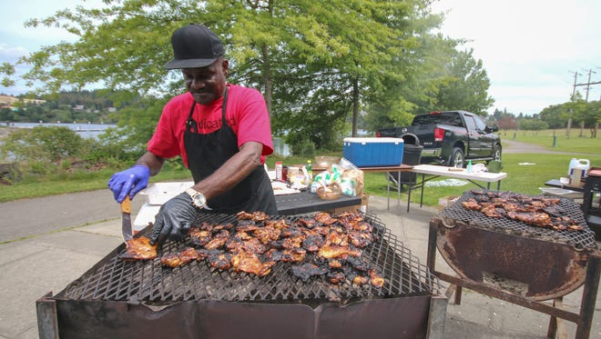 FILE — Donald Dye prepares chicken breasts at a previous Juneteenth celebration at Evergreen Rotary Park in Bremerton. While Juneteenth will be recognized as a state and federal holiday this year for the first time, members of the Black community in Bremerton have a long history of marking the day with a community celebration.