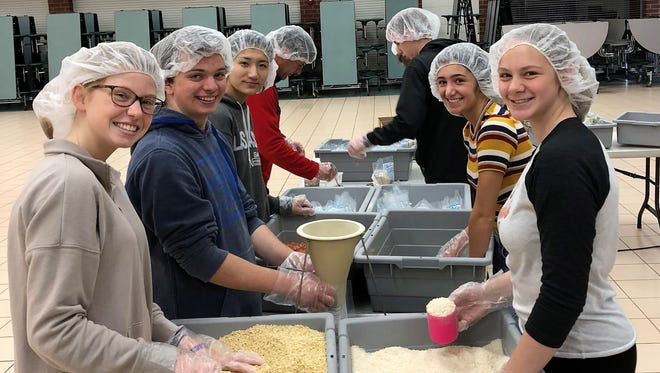 Northville High School students are pictured packaging food for hungry children around the world.