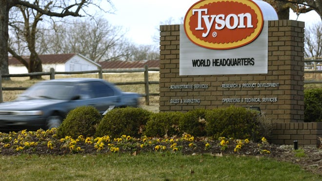 FILE - In this Jan. 29, 2006, file photo, a car passes in front of a Tyson Foods Inc., sign at Tyson headquarters in Springdale, Ark.  Tyson Foods plans to administer thousands of coronavirus tests per week at its U.S. facilities under an expanded effort to protect workers and keep plants running. The Springdale, Arkansas-based company, which processes about 20% of all beef, pork and chicken in the U.S., on Wednesday, July 29, 2020, said it will randomly test employees who have no symptoms as well as those with symptoms