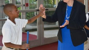 Superintendent Donna Hargens congratulating Malik Burt on his putt