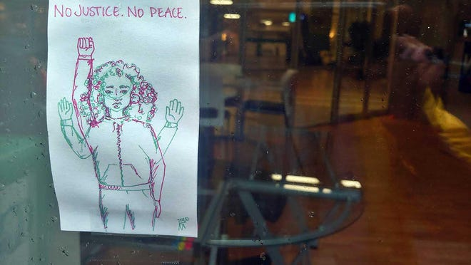 A handmade poster on the front window at the O. Marks Building on Middle Street in New Bern.