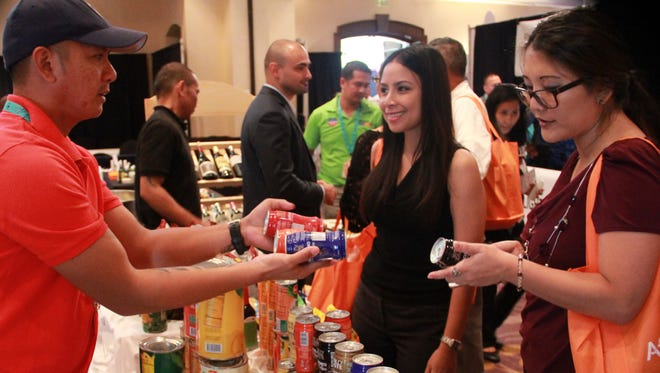 Rika Yamamoto and Carol Gaugob sample products from Fiesta Resort Guam at the Pacific Hotel and Restaurant Expo Sept. 30.