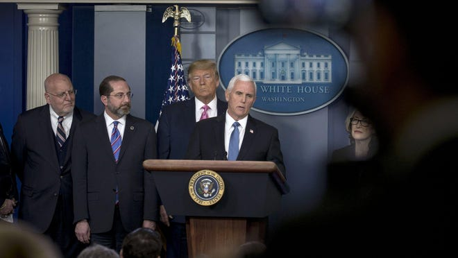 Vice President Mike Pence speaks as President Donald Trump looks on during a news conference on the coronavirus outbreak at the White House briefing room on Wednesday, Feb. 26, 2020. Trump named Pence to coordinate the government's response to the coronavirus, even as he repeatedly played down the danger to the U.S. of a widespread domestic outbreak.