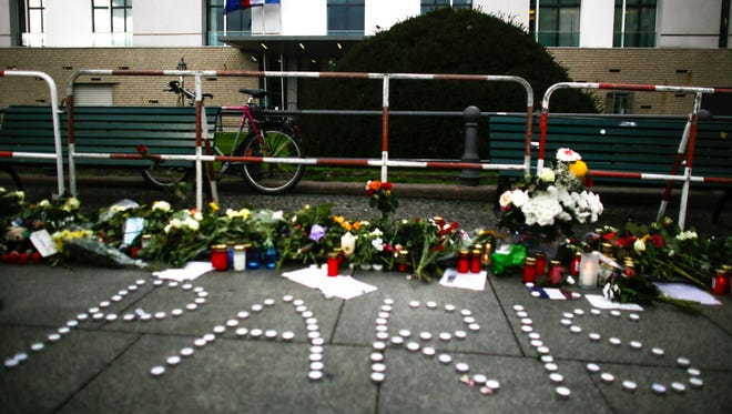 Flowers and candles are placed in front of the French Embassy in Berlin, on Nov. 14, 2015.