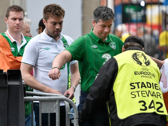 Spectators go through security checks as they enter the stadium prior to the Euro 2016 Group E soccer match between Ireland and Sweden at the Stade de France in Saint-Denis, north of Paris, France, Monday, June 13, 2016. (AP Photo/Martin Meissner)