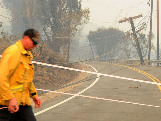 Firefighter Robert Bucho, of Orange County, tapes off Highway 150 near Santa Paula after winds knocked down power lines during the Thomas Fire in December 2017.