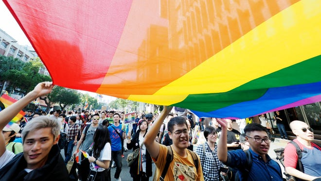 LGBT community members march while displaying a rainbow banner outside the Taiwan Parliament building in Taipei, Taiwan, Dec. 26, 2016.
