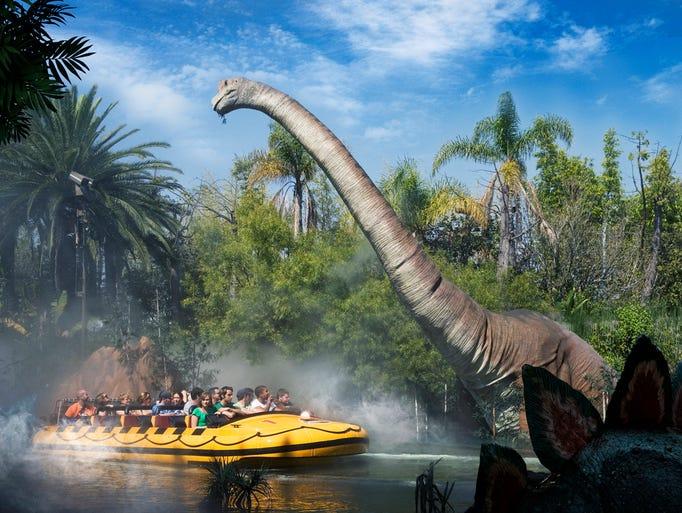 A 50-foot-tall dinosaur greets riders at Jurassic Park