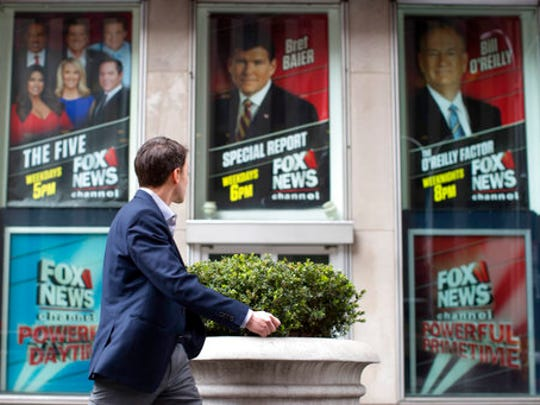 """A pedestrian walks past the News Corp. headquarters building in New York displaying posters featuring Fox News Channel personalities including Bill O'Reilly, right, on Wednesday, April 19, 2017. O'Reilly has lost his job at Fox News Channel following reports that five women had been paid millions of dollars to keep quiet about harassment allegations. 21st Century Fox issued a statement Wednesday that """"after a thorough and careful review of the allegations, the company and Bill O'Reilly have agreed that Bill O'Reilly will not be returning to the Fox News Channel."""