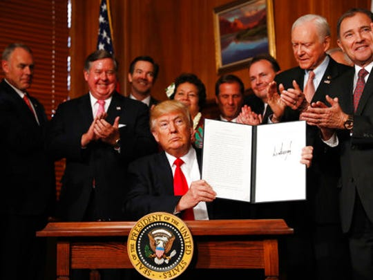 """President Donald Trump holds a signed Antiquities Executive Order during a ceremony at the Interior Department in Washington, Wednesday, April, 26, 2017. The president is asking for a review of the designation of tens of millions of acres of land as """"national monuments."""""""