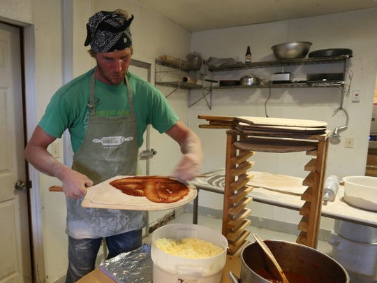 Co-owner Tony Schultz puts sauce on a pizza crust at Stoney Acres Farm near Athens, Friday, September 11, 2015.