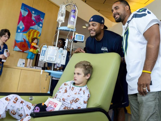 Garry Gilliam (left) and Jordan Hill (right), former Penn State football players who currently play for the NFL's Seattle Seahawks, pose for a picture with Harry Markey of York at Penn State Hershey Children's Hospital on Tuesday. Gilliam and Hill, who are each central Pennsylvania natives, took time to visit children and their families.