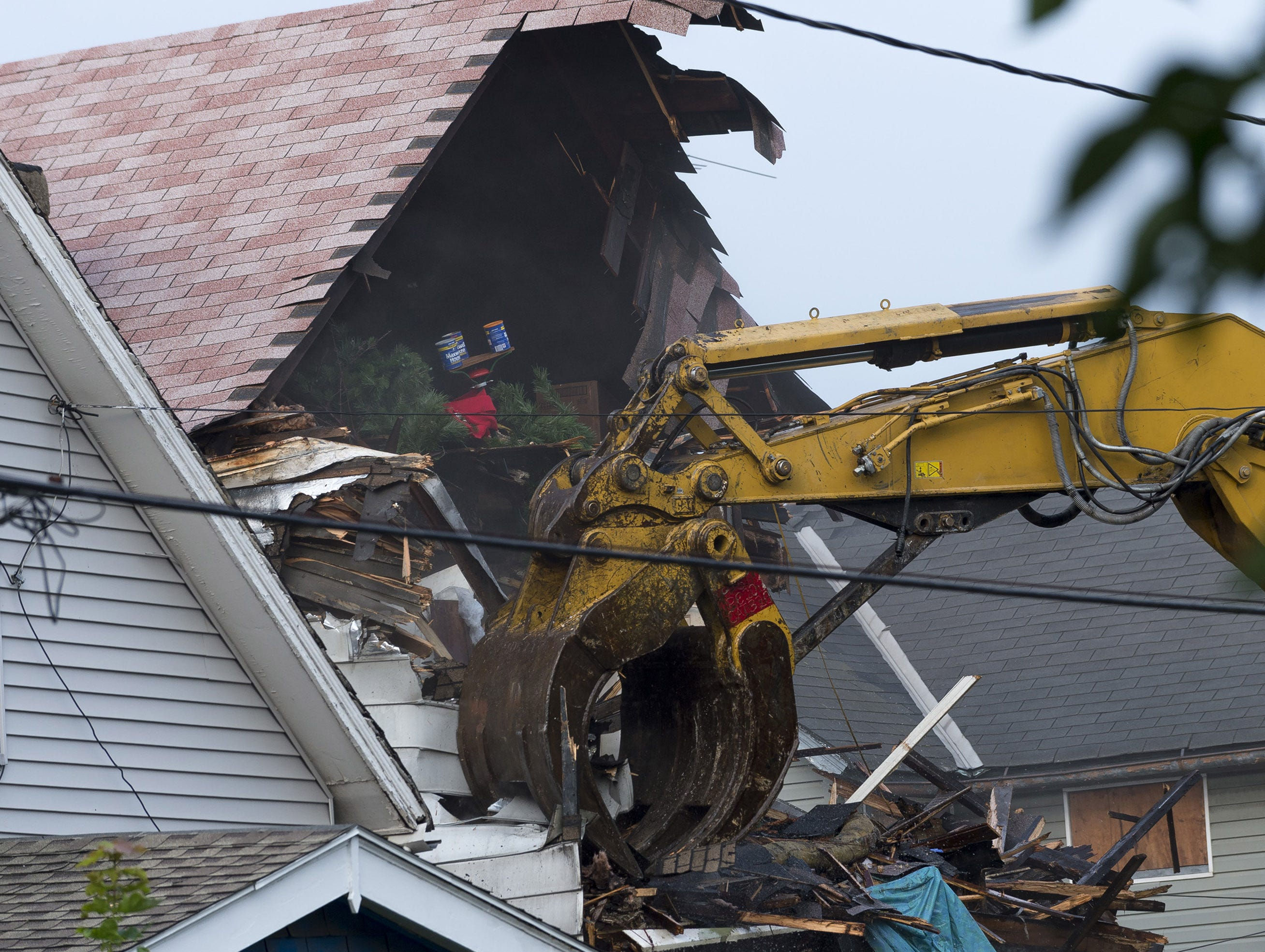 A crane demolishes the home of Ariel Castro on Aug. 7 in Cleveland. Castro, 53, held three women captive in the home for over a decade. He pleaded guilty last month to 937 charges including rape, kidnapping and aggravated murder. He was sentenced last week to life in prison plus 1,000 years.