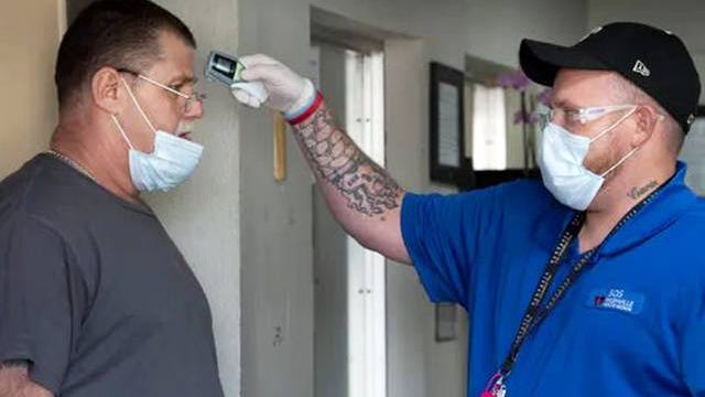 Rescue Mission guest William Treadwell has his temperature checked, by staffer Shane Durand, as he returns to the Nashville Rescue Mission on Wednesday in Nashville, Tenn. The mission has implemented procedures to help prevent the spread of COVID-19 at the facility.