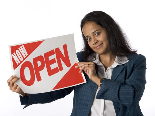Businesswoman holding now open sign