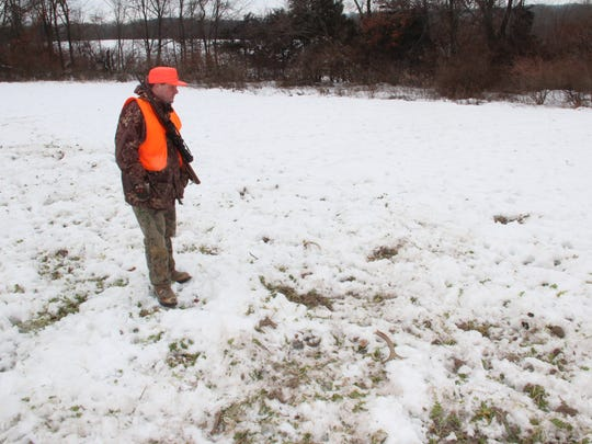 Jim Smukowski of Oconomowoc looks at a pair of antlers in a field near Richland Center on Dec. 27.