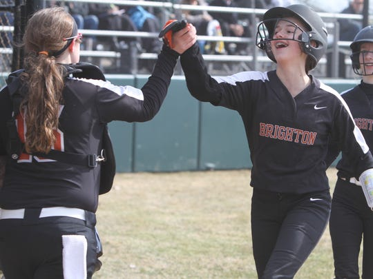 Brighton's Kayla Errer (right) celebrates with catcher Alexa Lamoreaux after scoring a run against Howell on Wednesday, April 11, 2018.