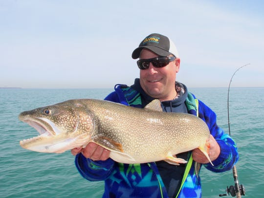 Brian Settele of Menomonee Falls, owner of Fish Chasers Guide Service, holds an 18-pound lake trout caught in the  Lake Michigan waters off Milwaukee.