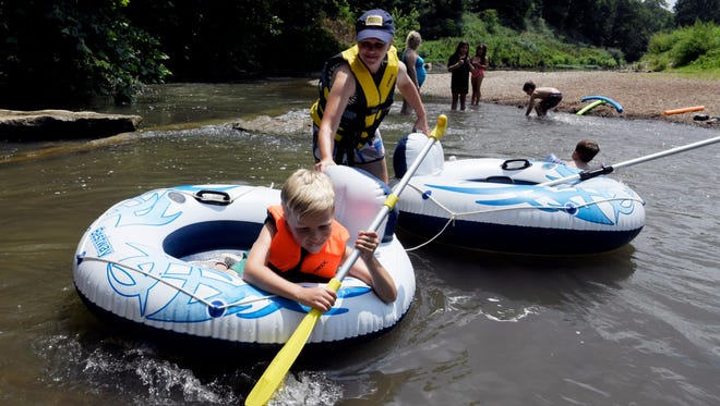 Charlie Devore and his mother Kiersten beat the heat rafting down the Harpeth River Friday, June 15, 2018, in Franklin, Tenn.