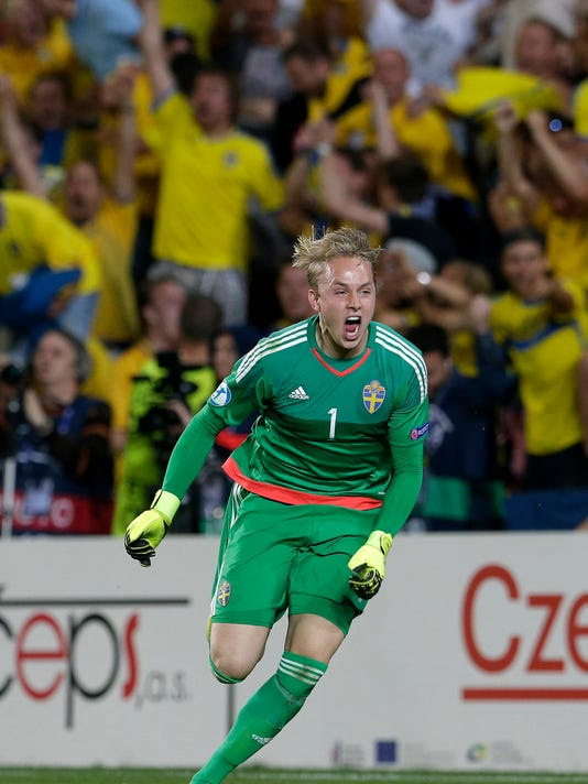 Sweden's goalkeeper Patrik Carlgren celebrates after catching the decisive penalty during the Euro U21 soccer championship final match between Sweden and Portugal, at the Eden stadium in Prague, Czech Republic, Tuesday, June 30, 2015. Sweden defeated Portugal on penalties with 4-3. (AP Photo/Petr David Josek)