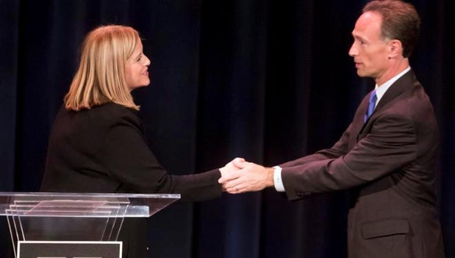 Mayoral candidates Megan Barry and David Fox shake hands following a debate at the Blair School of Music on Vanderbilt's campus Monday.