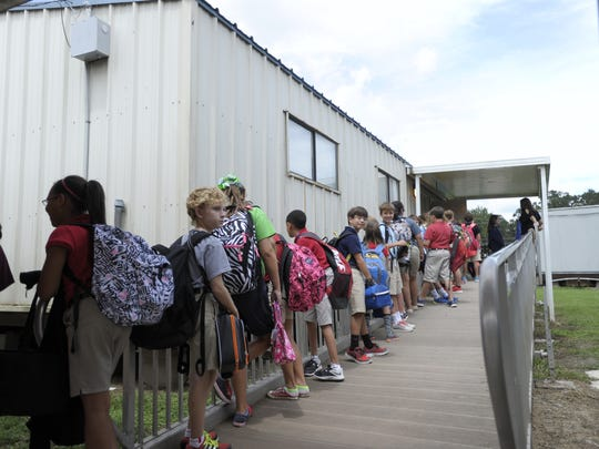 Students wait to enter a temporary classroom building in Lafayette Parish. The district would like to use tax proceeds to eliminate such temporary facilities.