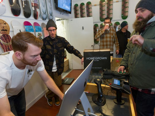 "Homegrown store owner Andrew Douglas, left , runs the register as Keith Ward, of Syracuse, scores a pair of the Nike SB Dunk High Premium ""Homegrown"" shoes in a coveted wooden box Friday morning."