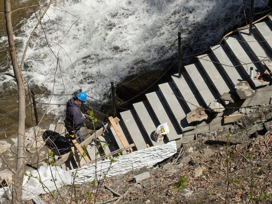 Chad Sanders of Ellis Hollow, working for Paolangeli Contractor, works near a white plastic form, lower left, used to shape shotcrete so that the surface of the structural wall looks like masonry next the Cascadilla Gorge trail.