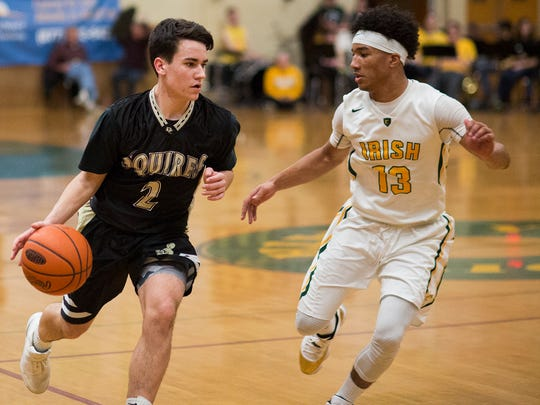 Delone Catholic's Brady Alexander, left, dribbles the ball while being defended by York Catholic's D'Andre Davis, right. York Catholic defeats Delone Catholic 75-40 in boys' basketball at York Catholic High School, Friday, January 27, 2017.