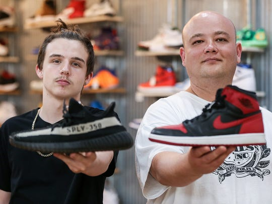 Grails Inc. employee Hadyn Mayes and owner Paul Zigrang hold up shoes outside the Washington Square Mall store. Mayes holds a Yeezy 350 shoe and Zigrang holds a Jordan 1.