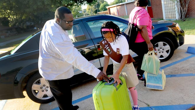 John Starkes (left) helps Ty'Keonna Winslow, 8, carry items into a Girl Scout meeting at Cherokee Park Elementary School in Shreveport. He and his wife, Felicia Holden-Starkes, have been raising the girl since her mother's disappearance.