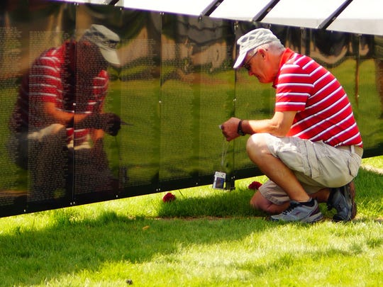 "A visitor finds a name at ""The Wall That Heals"" at The Highground."