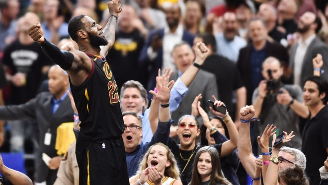 Cleveland Cavaliers forward LeBron James (23) stands on the scorer's table after hitting the final shot to win the game against the Toronto Raptors in game three of the second round of the 2018 NBA Playoffs at Quicken Loans Arena.