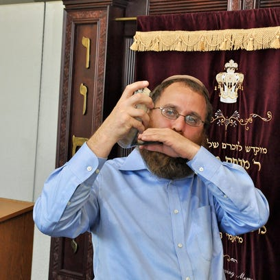 "Rabbi Fishel demonstrates how to sound a Shofar with his children at Chabad's ""Shofar Factory"" in preparation for the Jewish new year at The Carlisle Naples on Sept. 15. Rabbi Fishel and his children made ram's horn instruments, known as ""Shofar"" in Hebrew, and performed the traditional sequence of notes sounded on Rosh Hashanah, the Jewish new year."
