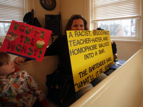 Rebecca Keen holds up a sign she brought to a recent City Council meeting to protest City Council presidential candidate and sitting Councilman John Di Mondi.