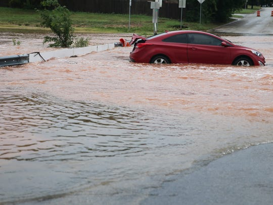 A car is stuck in a flooded section of Sul Ross Street
