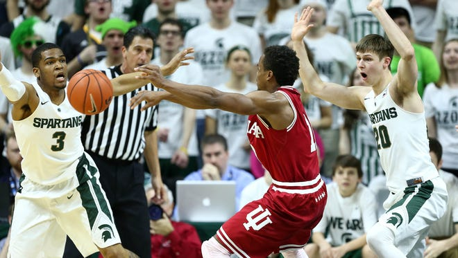 MSU's Alvin Ellis, left, and Matt McQuaid defend Indiana's Yogi Ferrell during the Spartans' 88-68 win over the Hoosiers Sunday at Breslin Center.