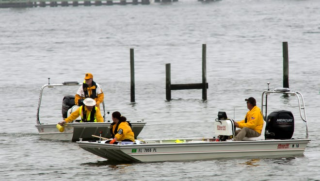 Military and civilian personnel search the waters Wednesday in Navarre, Fla., for victims of a military helicopter crash. Four Louisiana National Guardsmen are among 11 servicemen believed killed in the accident.