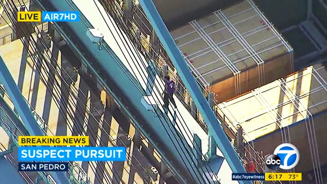 This frame from video provided by KABC-TV shows a man atop a container loading crane at the Port of Los Angeles, where he climbed after an hours-long high-speed police pursuit of his vehicle in Los Angeles.